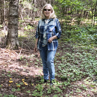 Ms Judy standing in the forest